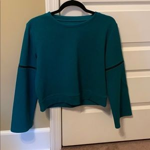 Green Zella that is cropped with long sleeves,